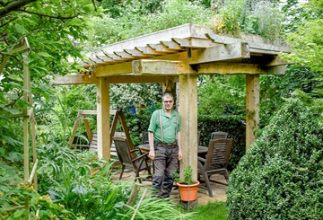 Cleared trees provide materials for creating a living-roof arbour